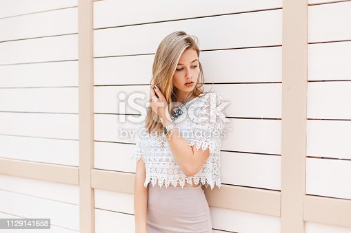 578791454istockphoto Elegant young woman in a fashionable beige skirt in a white lace blouse with an ornament is standing near a vintage white wooden wall outdoors on a sunny spring day. Glamor girl enjoys the weekend. 1129141658