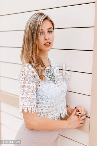 578791454istockphoto Elegant young woman in a white lace blouse with a stylish beige skirt with a luxurious shiny necklace posing near vintage wooden wall outdoors. Beautiful girl on a walk. 1129141679