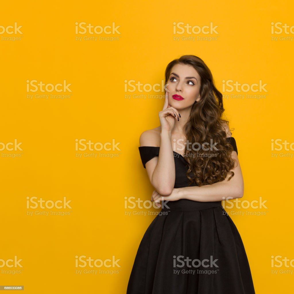 Elegant Young Woman In Black Dress Is Thinking And Looking Up royalty free stockfoto