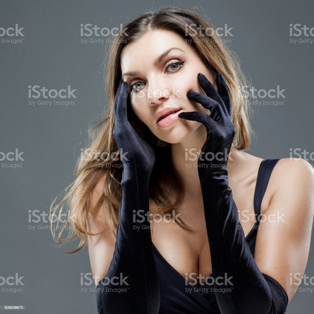 Elegant young woman in long black gloves. Portrait on gray background stock photo