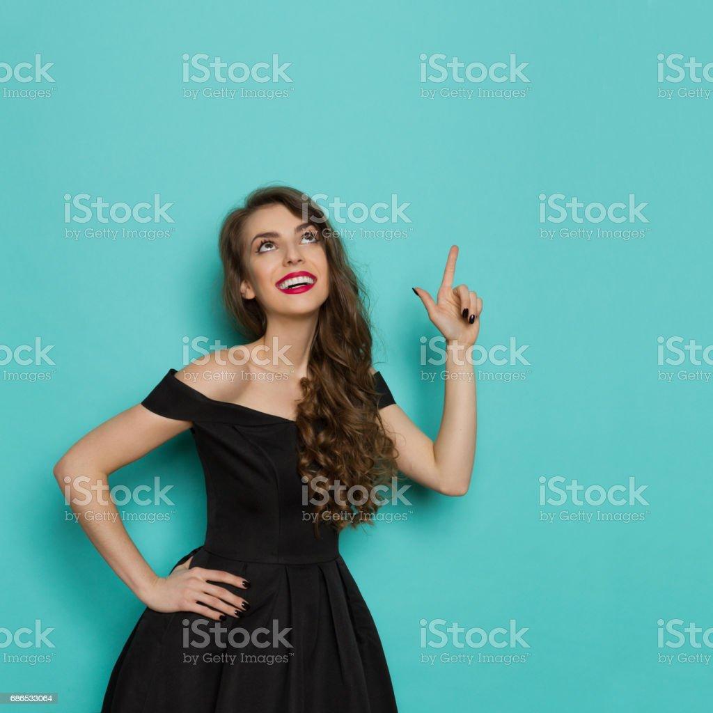 Elegant ung kvinna leende, tittar upp och pekar royaltyfri bildbanksbilder