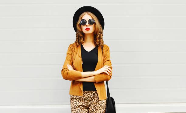 elegante junge frau trägt ein retro-eleganten hut, sonnenbrille, braune jacke und schwarze handtasche kupplung auf grauem hintergrund - bedruckte leggings stock-fotos und bilder