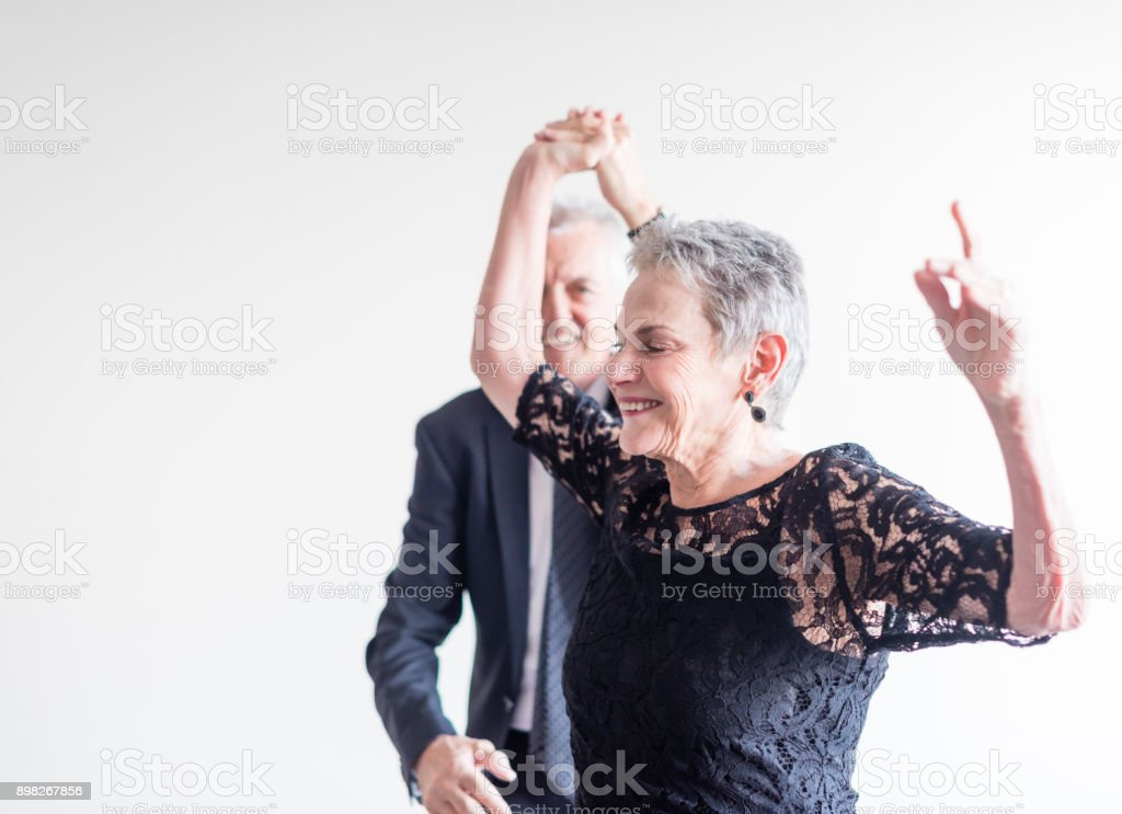Elegantly dressed couple dancing exuberantly foto stock royalty-free