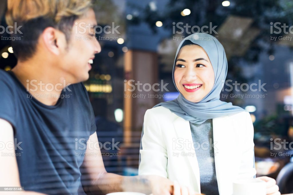 Elegantly dressed hijabi girl meeting her friend at a cafe stock photo