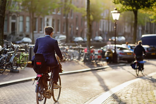 AMSTERDAM, NETHERLANDS - SEPTEMBER 18, 2018: An elegantly dressed man rides a Bicycle in the center of Amsterdam. Bicycle capital of Europe.