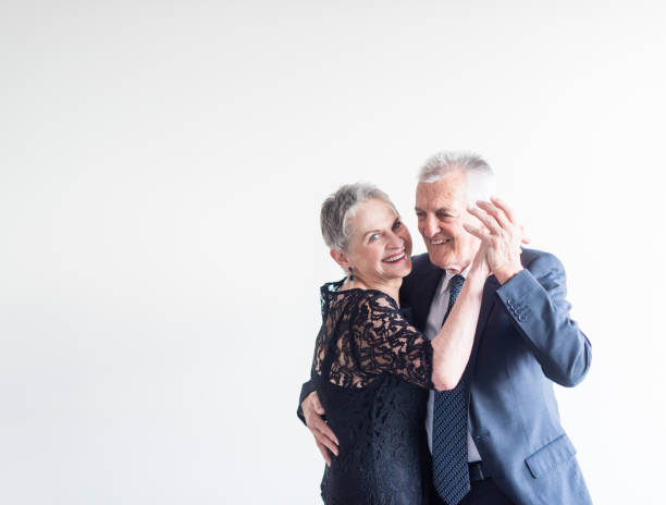 elegantly dressed older couple dancing - senior valentine stock photos and pictures