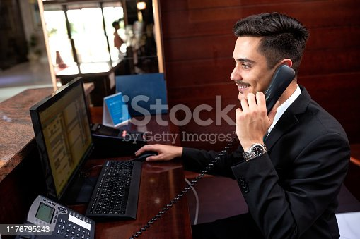Elegantly dressed receptionist holding a headphone, travel and catering concept