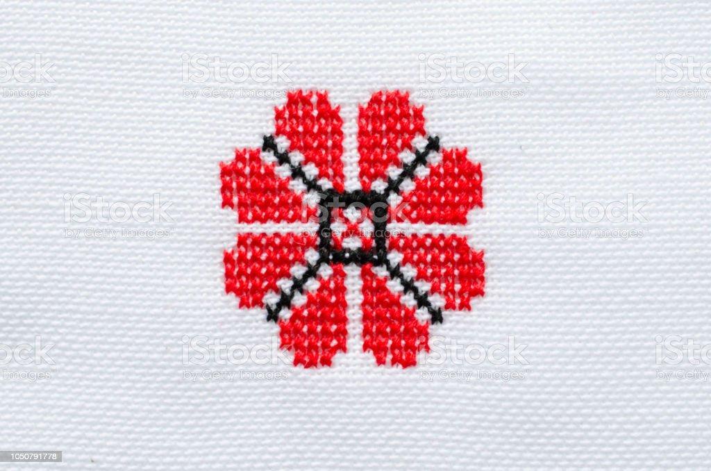 Elemento artesanal bordado em linho branco por fios de algodão vermelho e preto. - foto de acervo