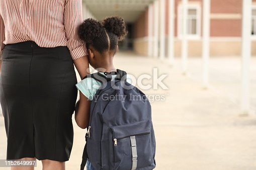 Elementary age, African American girl holds mom or teacher's hand before school begins.  She wears a backpack and clings to mom with uncertainty about starting school.