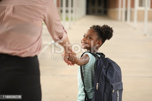 Elementary age, African American girl holds mom or teacher's hand before school begins.  She wears a backpack and big smile as she excitedly prepares for her very first day of school.