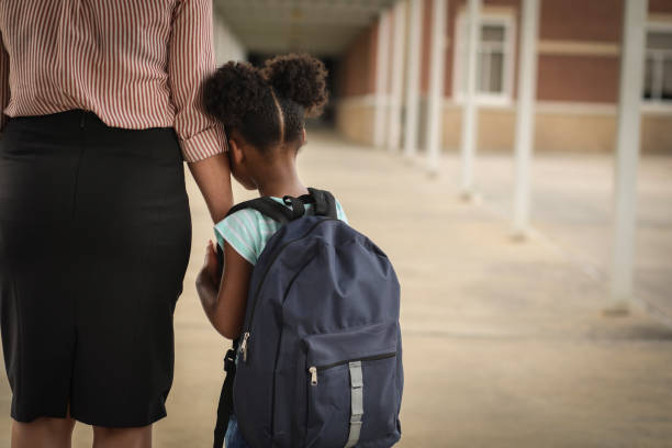 Elementary, African American girl with mom on first day of school. stock photo