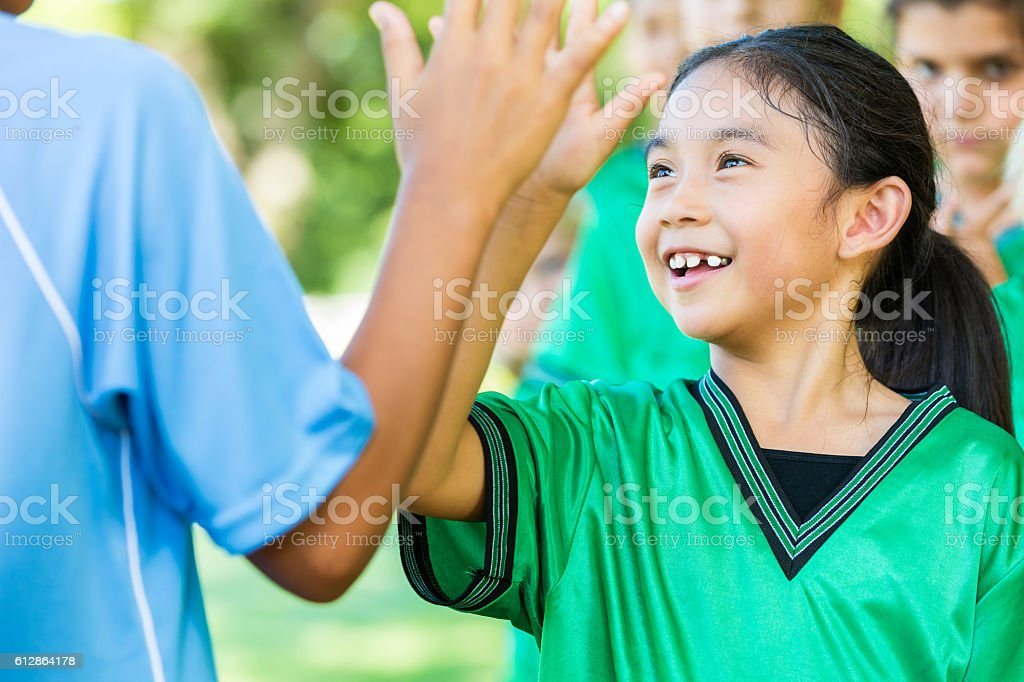 Elementary age Asian female soccer player greets opposing team stock photo