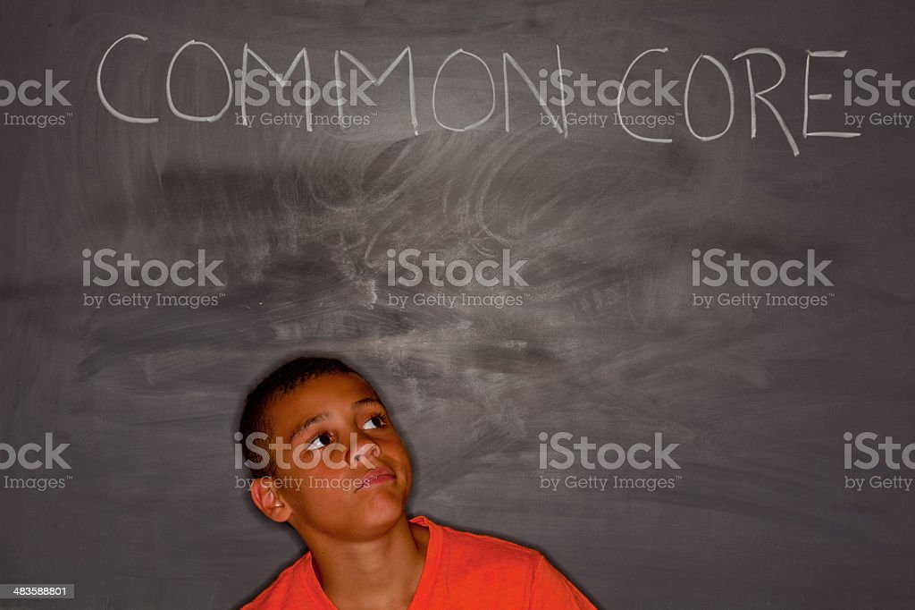 Elementary age boy in front of chalkboard with 'common core' stock photo