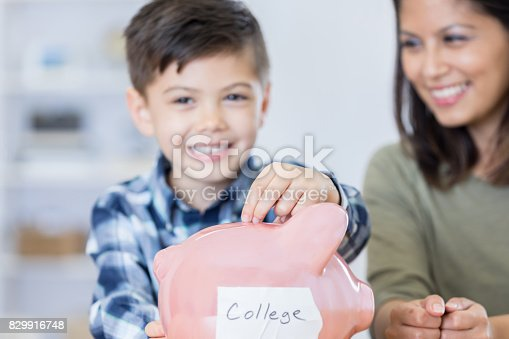 istock Elementary age boy saves for college 829916748