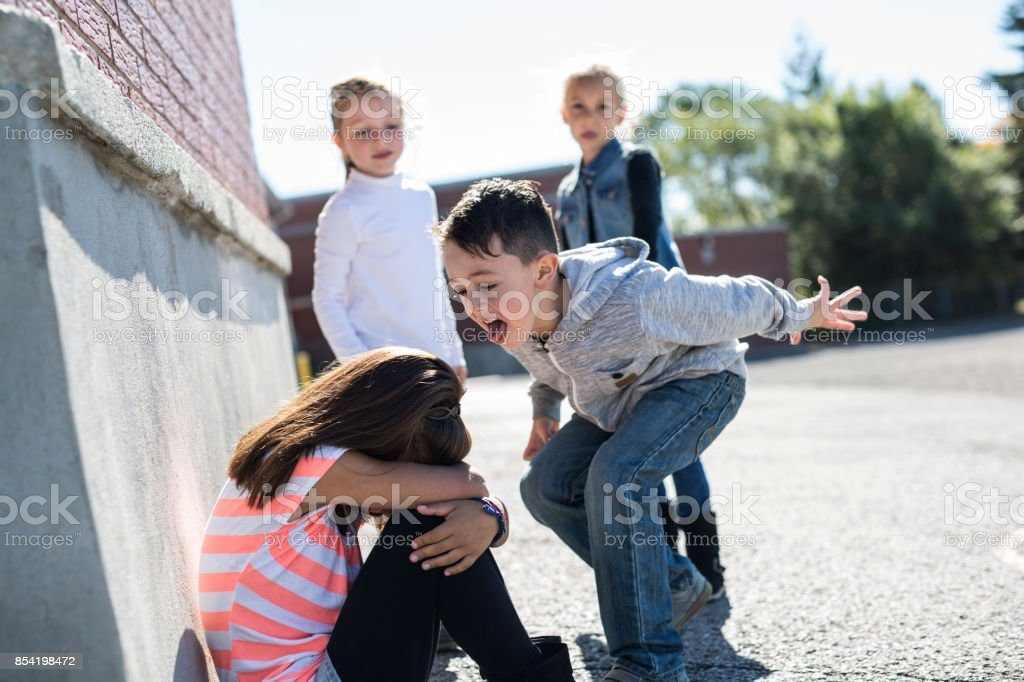 Elementary Age Bullying in Schoolyard sad moment Elementary Age Bullying in Schoolyard Anger Stock Photo