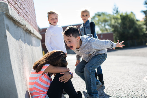Elementary Age Bullying In Schoolyard Stock Photo - Download Image Now