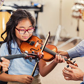 A smiling elementary age girl looks down as she plays the violin in music class at school.  An unrecognizable teacher reaches toward her to help with proper positioning.