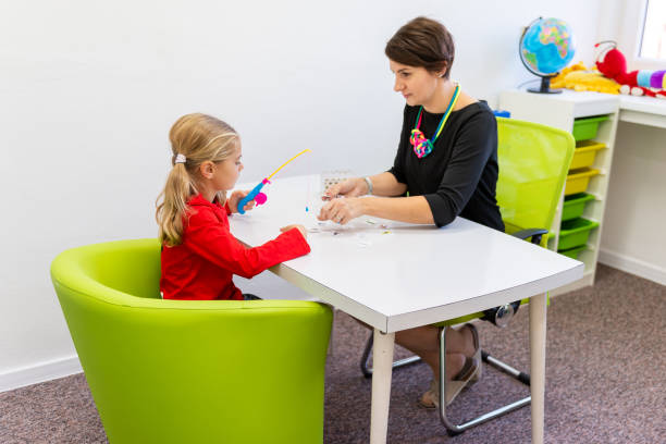 Elementary Age Girl in Child Occupational Therapy Session Doing Playful Exercises With Her Therapist. Elementary Age Girl in Child Occupational Therapy Session Doing Playful Exercises With Her Therapist. learning difficulty stock pictures, royalty-free photos & images