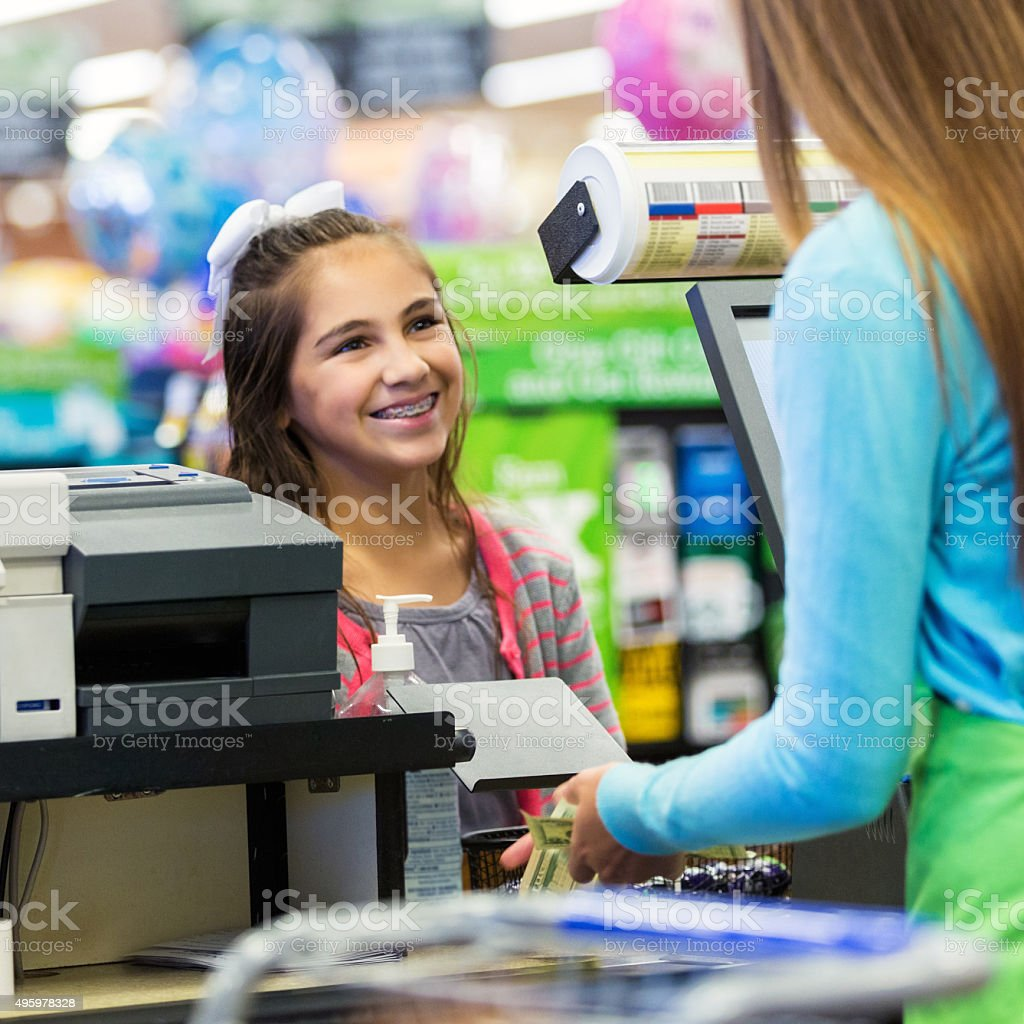 Elementary age girl paying for something at grocery store stock photo