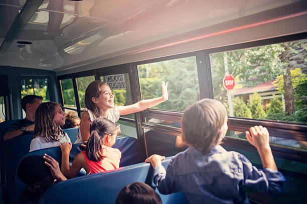 elementary age girl saying hello from a school bus. - autobuses escolares fotografías e imágenes de stock