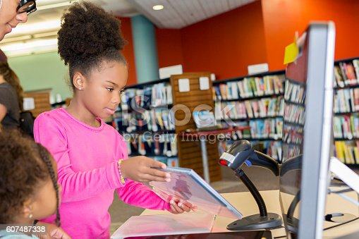 African American elementary age girl with natural hair is scanning a book as her mother and toddler sister watches. Family is standing at a desk with a computer in the library and scanning books.