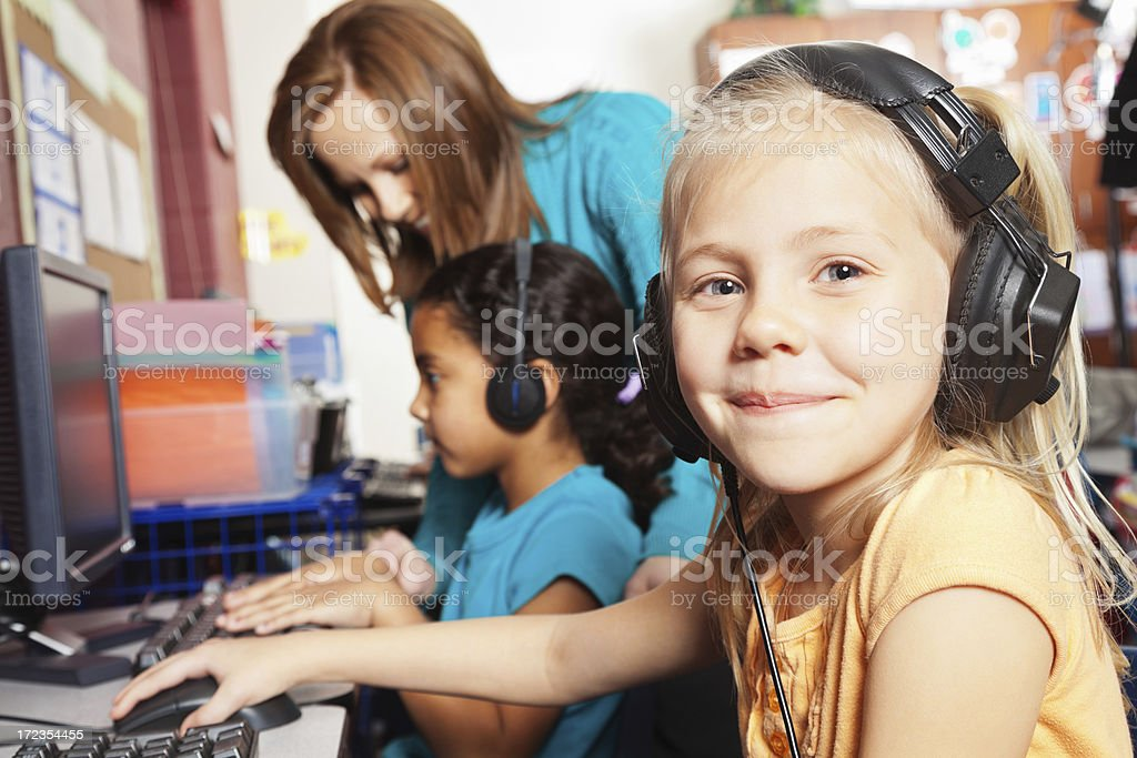 Elementary age girl using headphones in school computer lab royalty-free stock photo