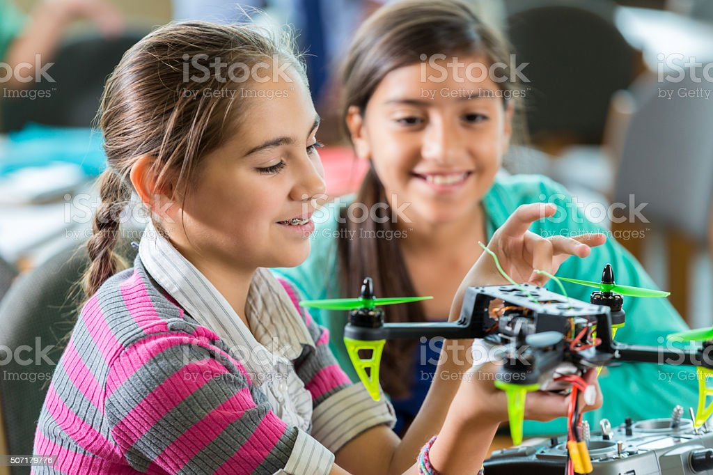 Elementary age Hispanic little girls using drone in science class stock photo