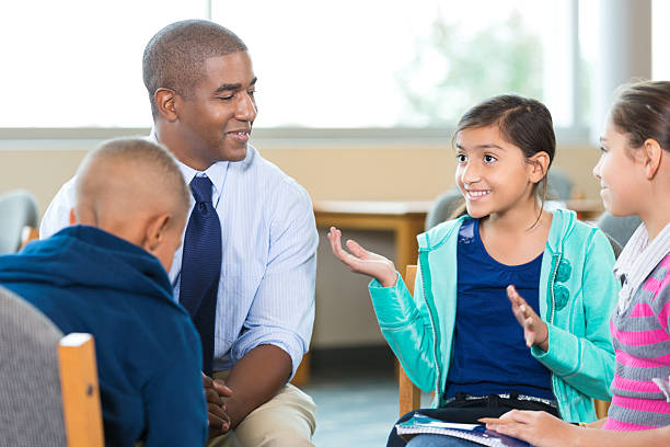 elementary age kids talking to counselor during group therapy session - school counselor stock photos and pictures