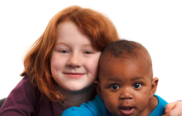elementary age redhead girl hugging 6month old adopted black sister stock photo