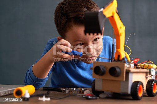 6-7 years old cute boy builds robot for his school project