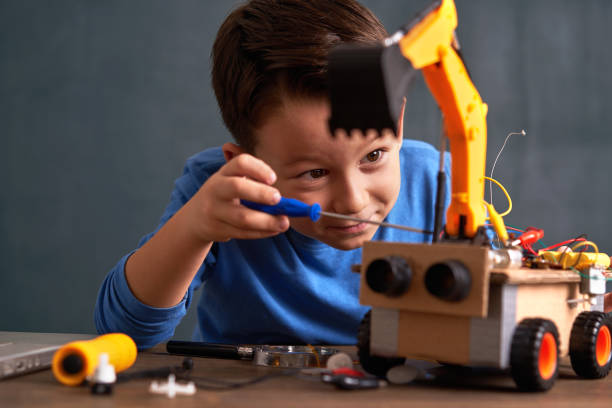 Elementary age school boy builds robot 6-7 years old cute boy builds robot for his school project stem topic stock pictures, royalty-free photos & images