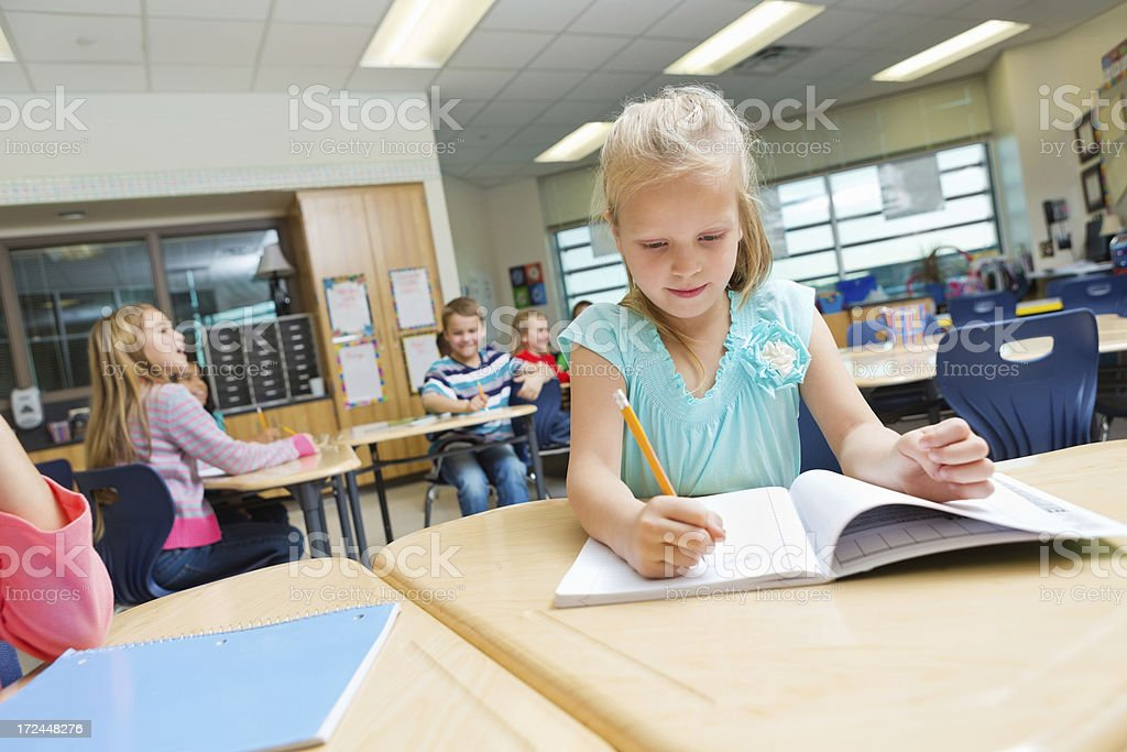 Elementary age school girl writing in classroom