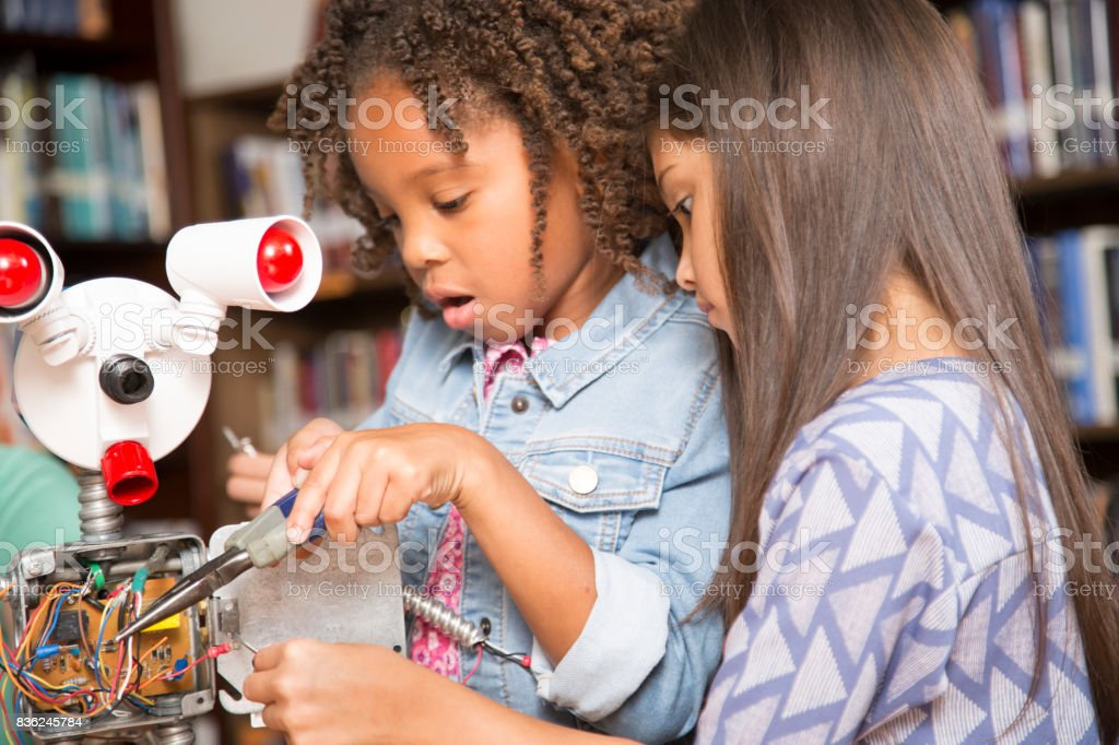 Elementary age school girls build robot in technology class. stock photo