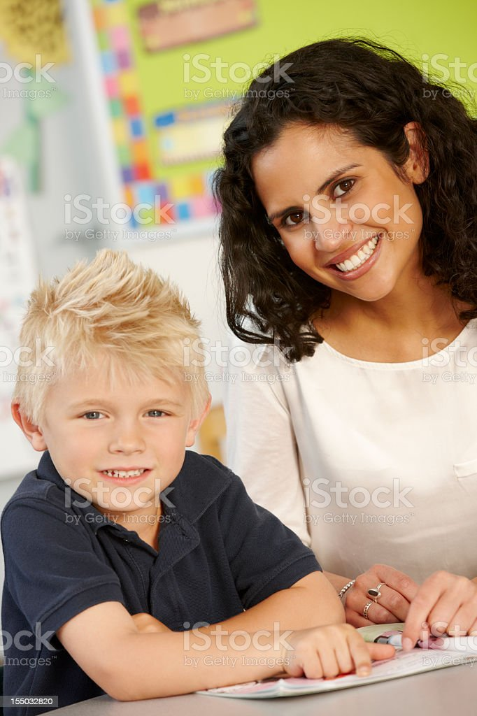 Elementary Age Schoolboy Reading Book In Class With Teacher royalty-free stock photo