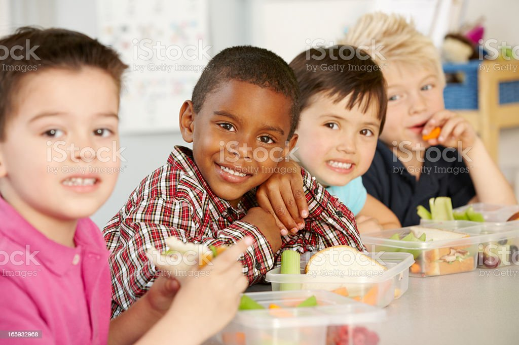 Elementary Age Schoolchildren Eating Healthy Packed Lunch stock photo