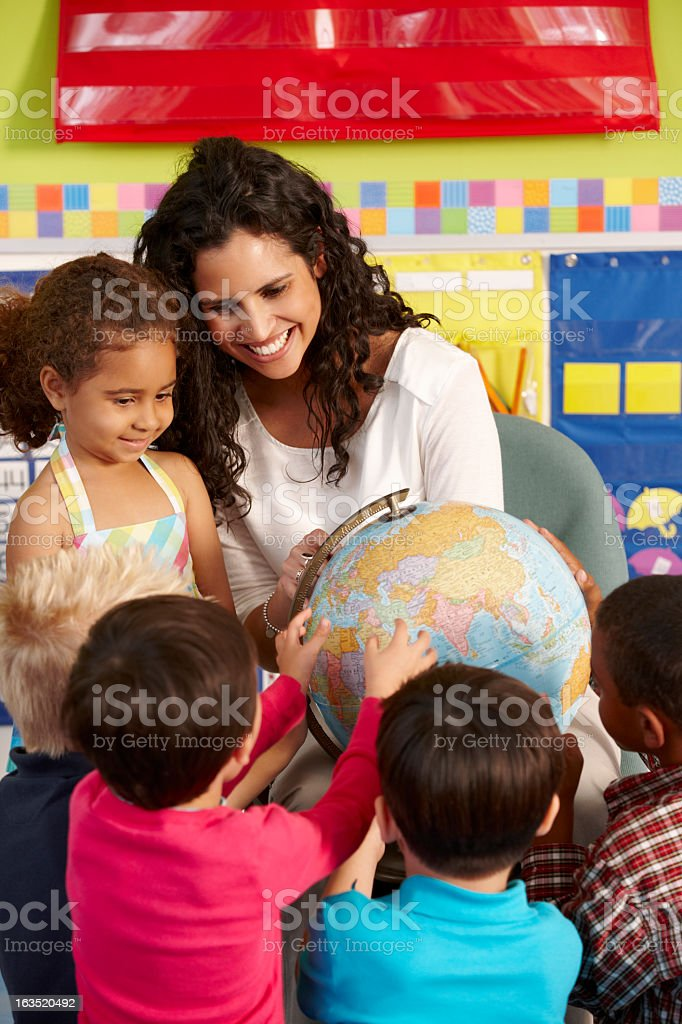 Elementary Age Schoolchildren In Geography Class With Teacher stock photo