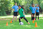 Asian elementary age soccer athlete confidently kicks the ball around orange practice cones. She is wearing a green uniform. Players in blue uniforms are lined up behind her as well as her young adult Caucasian female coach.
