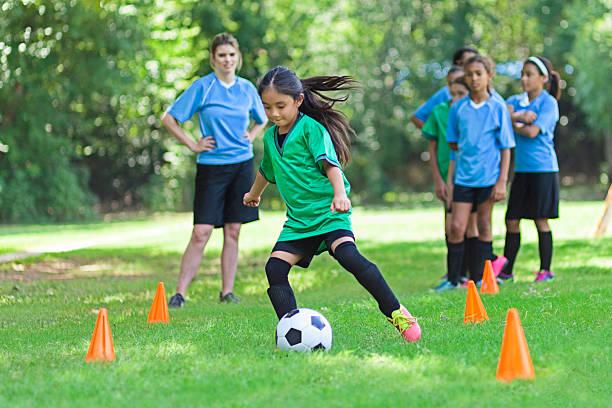 Elementary age soccer athlete kicks ball around cones stock photo