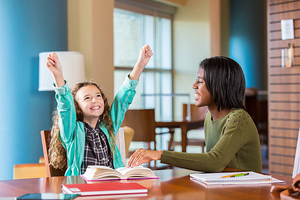 Elementary age student celebrating completing homework with tutor stock photo