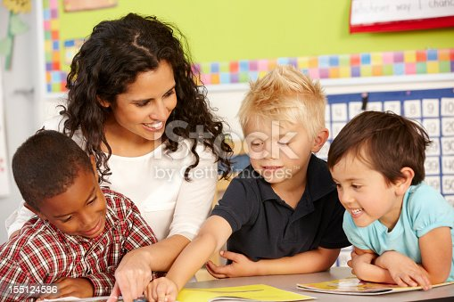 istock Elementary aged boys learning in classroom with teacher 155124586