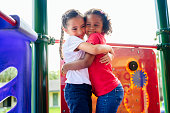 Affectionate young female Hispanic best friends hugging outdoors on playground equipment during school recess break.