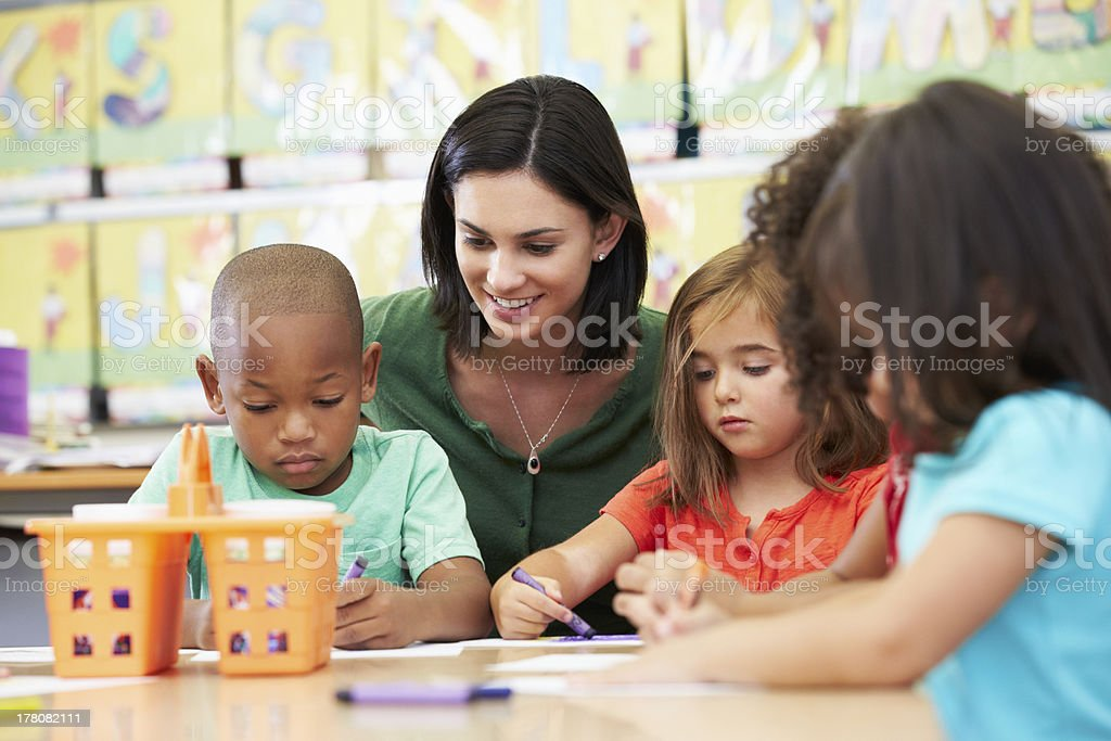 Elementary art class drawing with teacher at table royalty-free stock photo