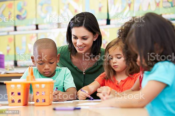 Elementary Art Class Drawing With Teacher At Table Stock Photo - Download Image Now