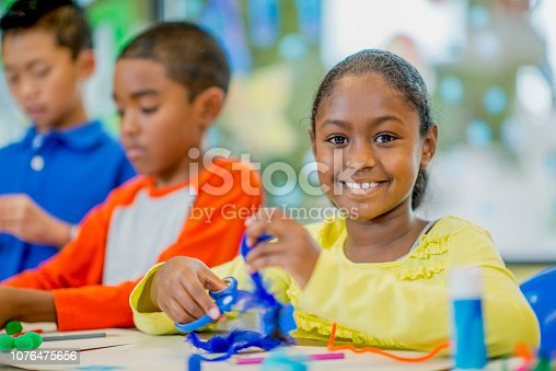 A young girl is sitting at a table and playing with pipe cleaners. She is smiling at the camera. There are two boys sitting beside her.