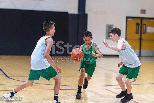 A young African American boy dribbles through two defenders and tries to score.
