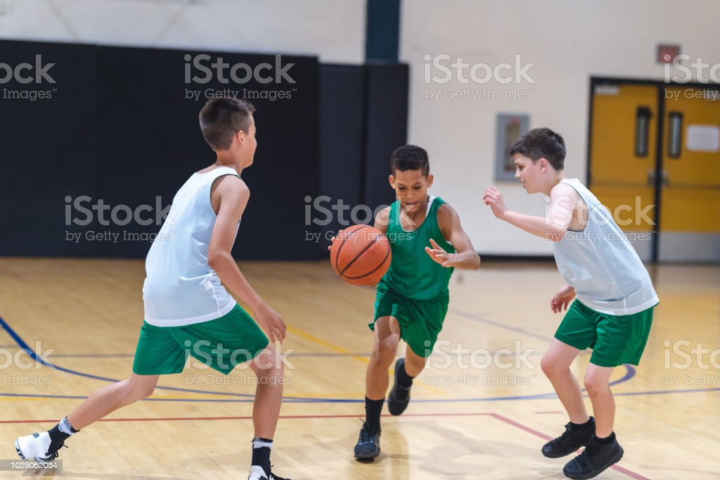 Elementary boys playing basketball stock photo