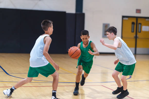 Elementary boys playing basketball A young African American boy dribbles through two defenders and tries to score. basketball ball stock pictures, royalty-free photos & images