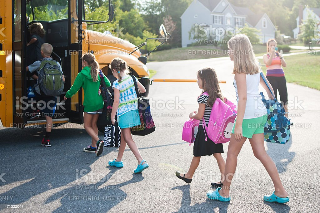 Elementary Children Enter Bus on First Day of School stock photo