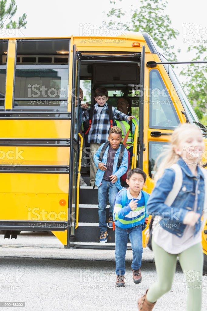 Elementales niños salir del autobús escolar - foto de stock