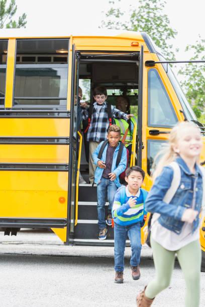 elementales niños salir del autobús escolar - autobuses escolares fotografías e imágenes de stock